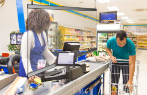 Male customer in casual putting products from cart to counter. Buyer shopping in supermarket. Grocery shopping concept